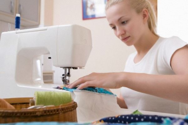 Young woman sits making patchwork at sewing machine --- Image by © Vladimir Godnik/moodboard/Corbis